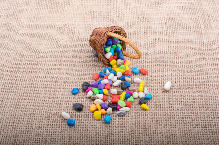 Basket of colorful pebbles spill on canvas background
