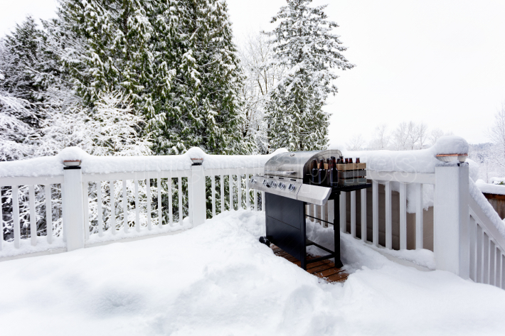 BBQ cooker with beer during winter time on home outdoor deck