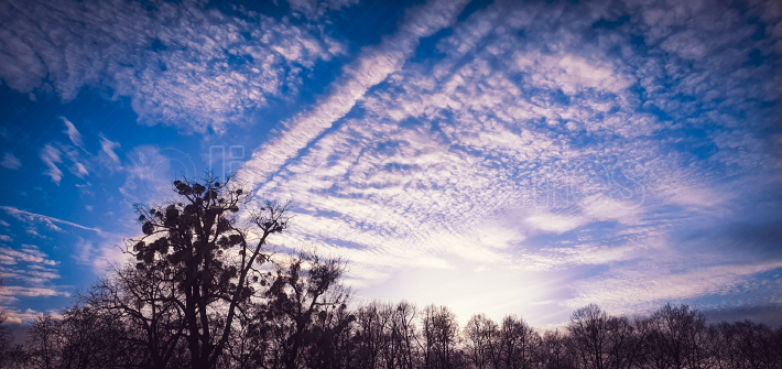 Beautiful altocumulus clouds with sunshine rays and blue sky