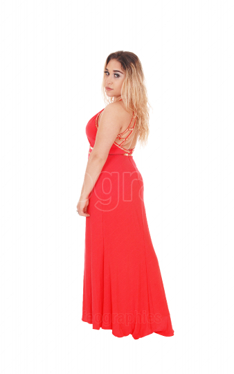 Beautiful blond woman standing in red dress in profile