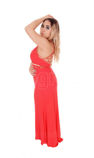 Beautiful blond woman standing in red dress with hand on head