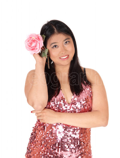 Beautiful Chinese woman holding a pink rose to her hair