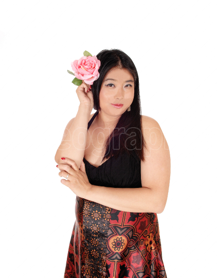 Beautiful Chinese woman holding rose to her hair