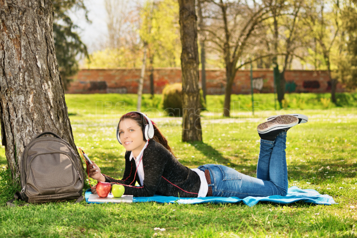 Beautiful female student listening music in the park