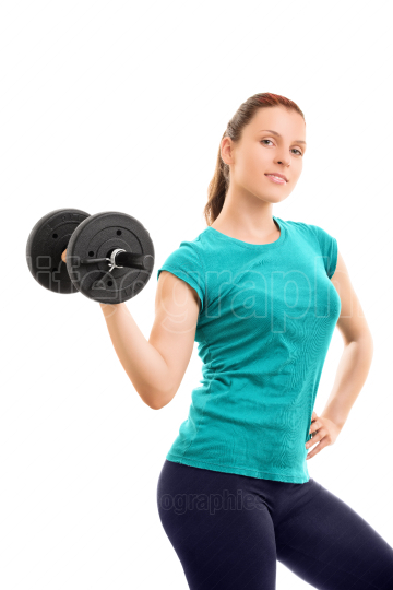 Beautiful fit girl smiling and holding a dumbbell