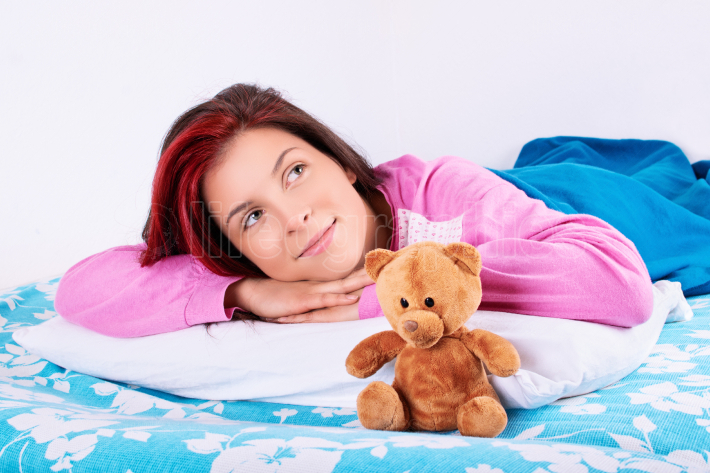 Beautiful girl in pajamas with her teddy bear daydreaming