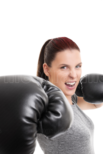 Beautiful girl with boxing gloves punching the camera