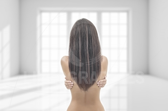 Beautiful girl with long hair, sit facing a lighted window with his back to the camera