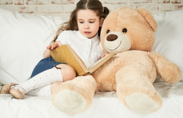 Beautiful little girl reading to her teddy bear toy friend