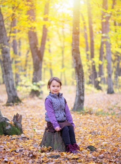 Beautiful little girl stands on a trunk of tree smiling