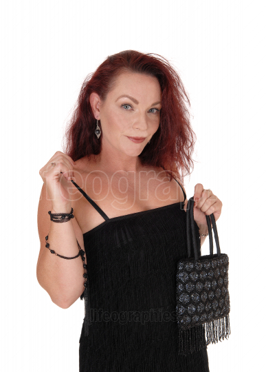 Beautiful woman in a black dress holding her purse