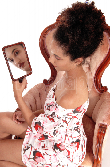 Beautiful woman looking into a hand held mirror