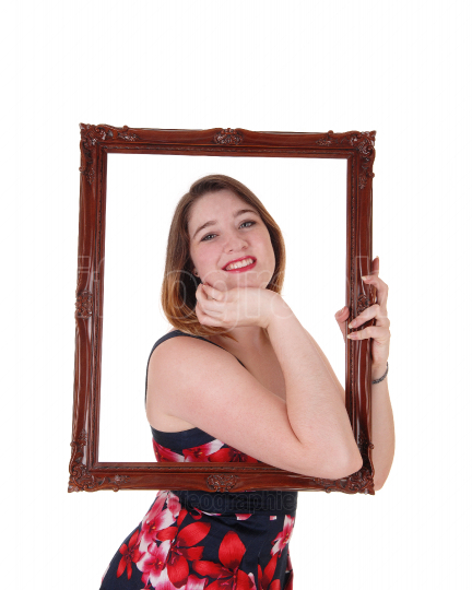 Beautiful woman looking trough a picture frame