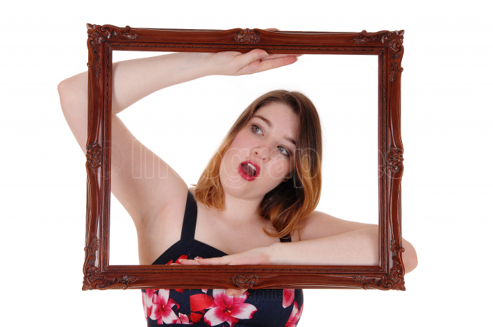 Beautiful woman looking trough a picture frame is surprised