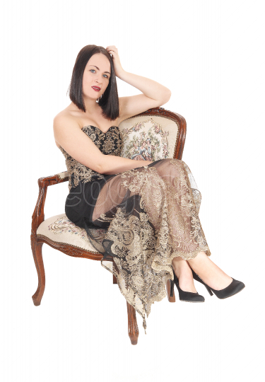 Beautiful woman sitting in armchair in a long dress