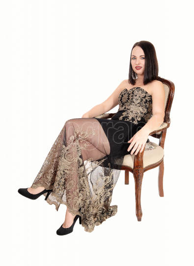 Beautiful woman sitting in armchair with a long dress