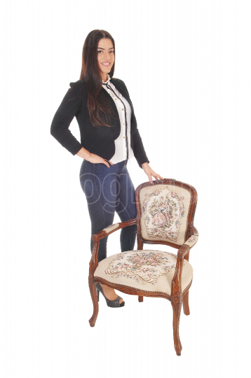 Beautiful woman standing behind an old chair