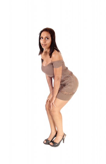 Beautiful woman standing in brown dress looking at camera