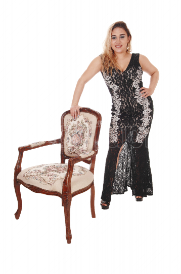 Beautiful woman standing with an antic armchair