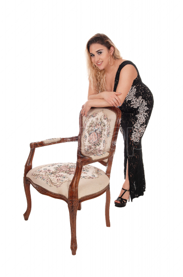 Beautiful woman standing with an antic armchair and dress
