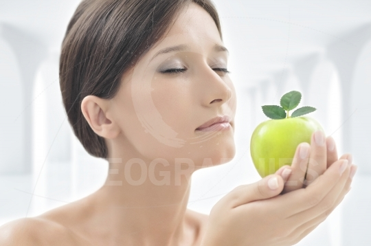 Beautiful woman with an apple in her hands