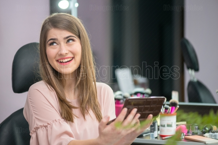 Beautiful woman with hairstyle and makeup looking at the mirror in  a beauty salon
