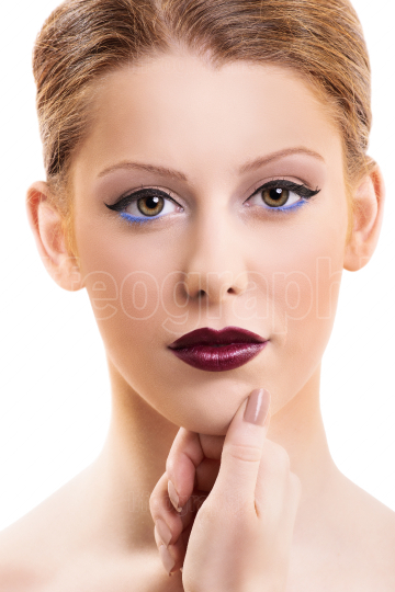 Beautiful woman with make up touching her face