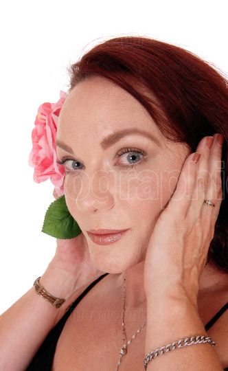 Beautiful woman with red hair and a pink rose
