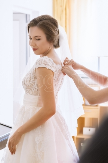 Beautiful young bride in wedding dress in living room