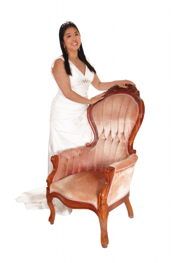 Beautiful young Chinese bride standing on an armchair