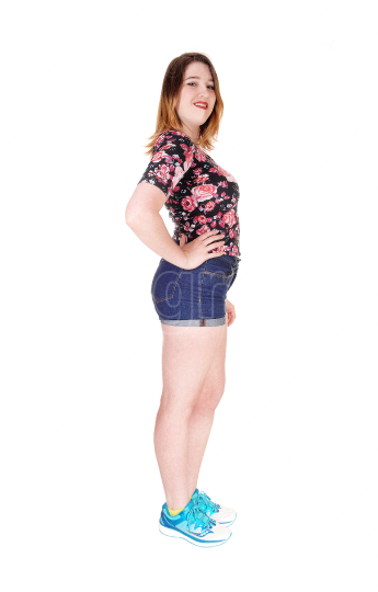 Beautiful young woman standing in profile in shorts