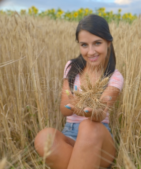 Beautiful young woman who offers a bouquet of wheat