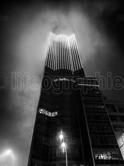 Black and white photograph of a skyscraper in fog