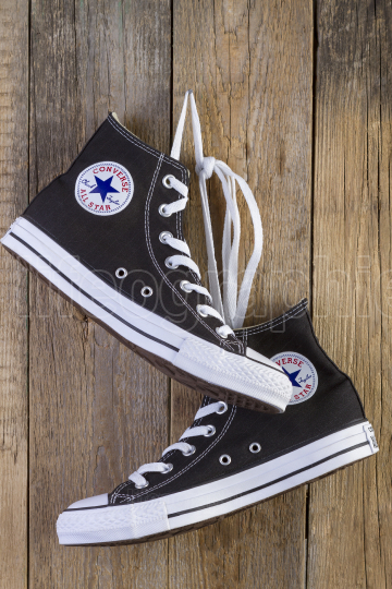 Black Converse sneakers on wood