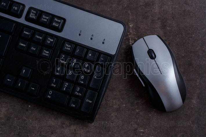 Black keyboard and black and grey computer mouse on grey marble