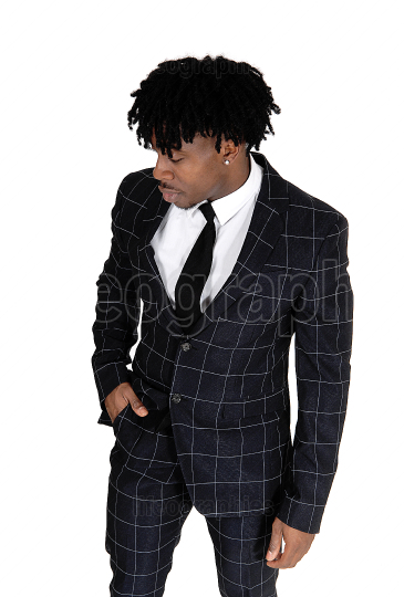 Black man in a dark suit standing in the studio with fussy black
