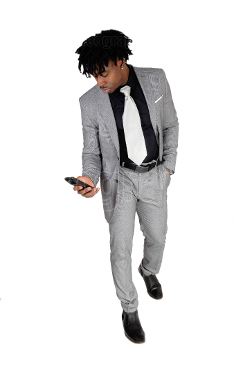 Black man standing looking at his cell phone