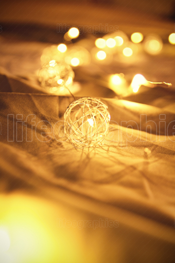 Blurred golden Christmas lights on rumpled bed sheets