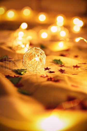 Blurred golden Christmas lights with decorations on rumpled bed sheets