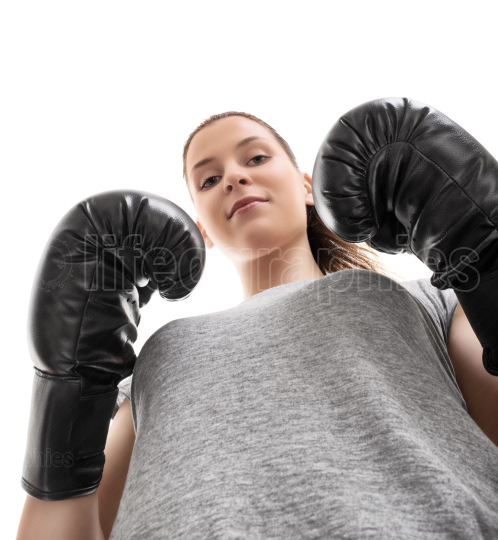 Bottom up view of a beautiful young woman with boxing gloves