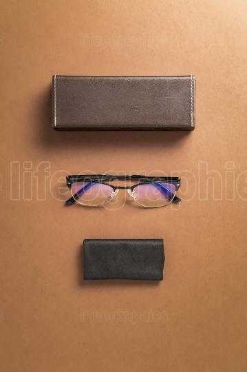 Brown eyeglasses, eyewear frame and fabric over brown background