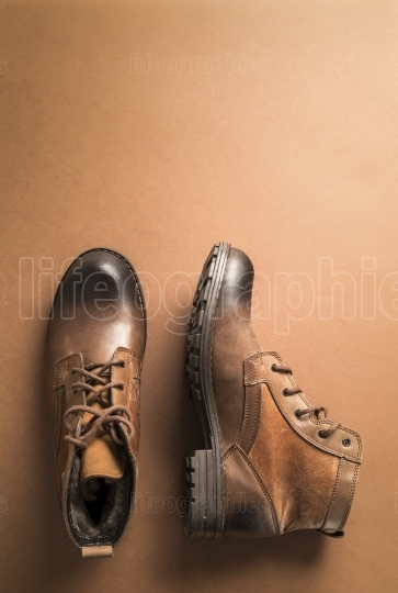 Brown leather boots over brown background,above view with copy space for text or other
