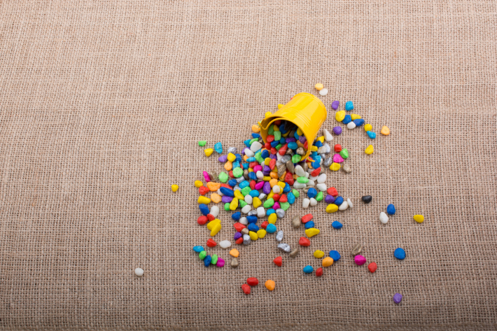Bucket of colorful pebbles spill on canvas background