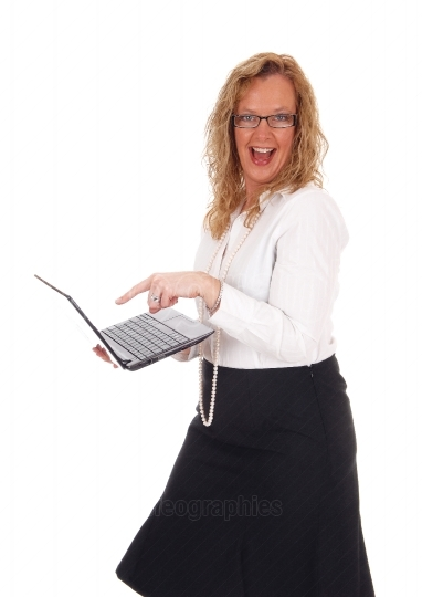 Business woman laughing at laptop.