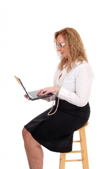 Business woman sitting and working with laptop.