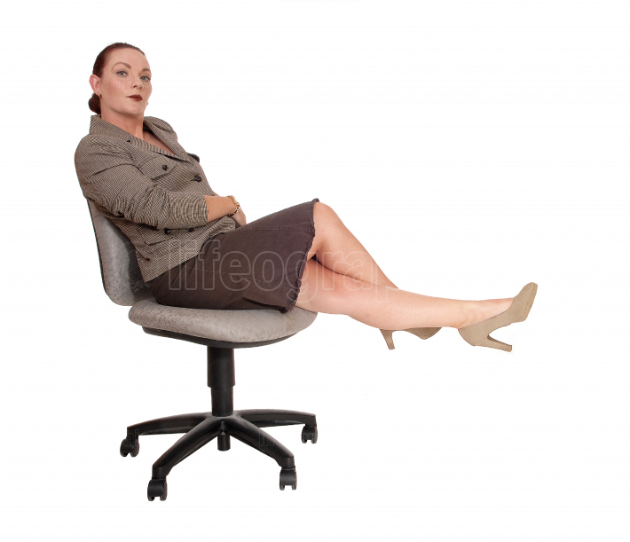 Business woman sitting relaxing on her chair, legs up