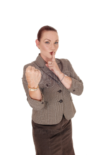 Business woman standing with her finger over mouth