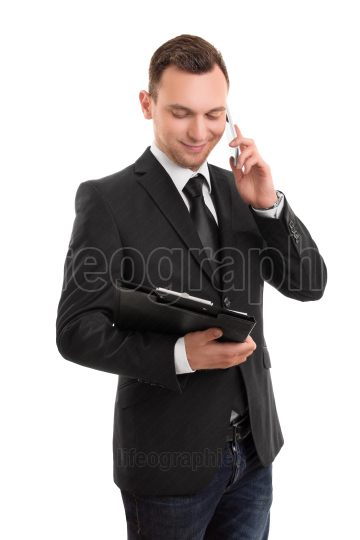 Businessman holding a notepad and talking on a phone