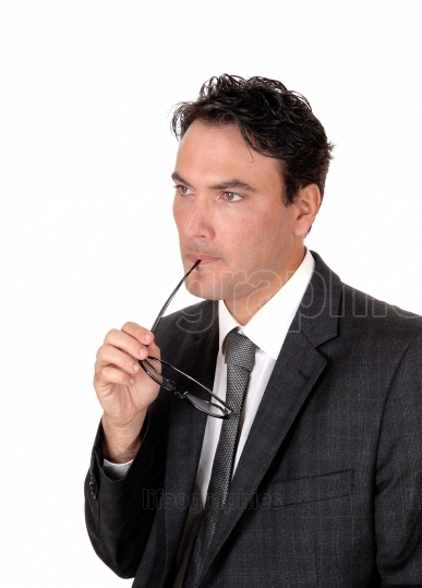 Businessman thinking with glasses in his mouths