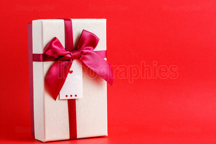 Cardboard biodegradable gift box with bows on red background